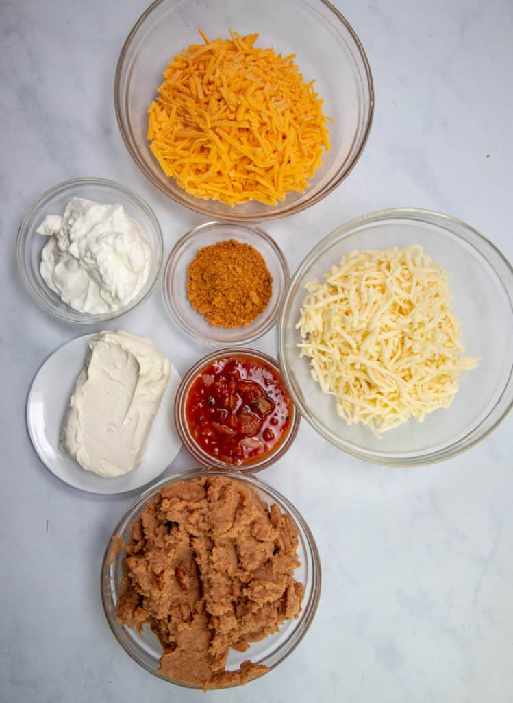 cream cheese, sour cream, refried beans, salsa, taco seasoning, shredded cheddar, shredded Monterey jack cheese, diced cilantro