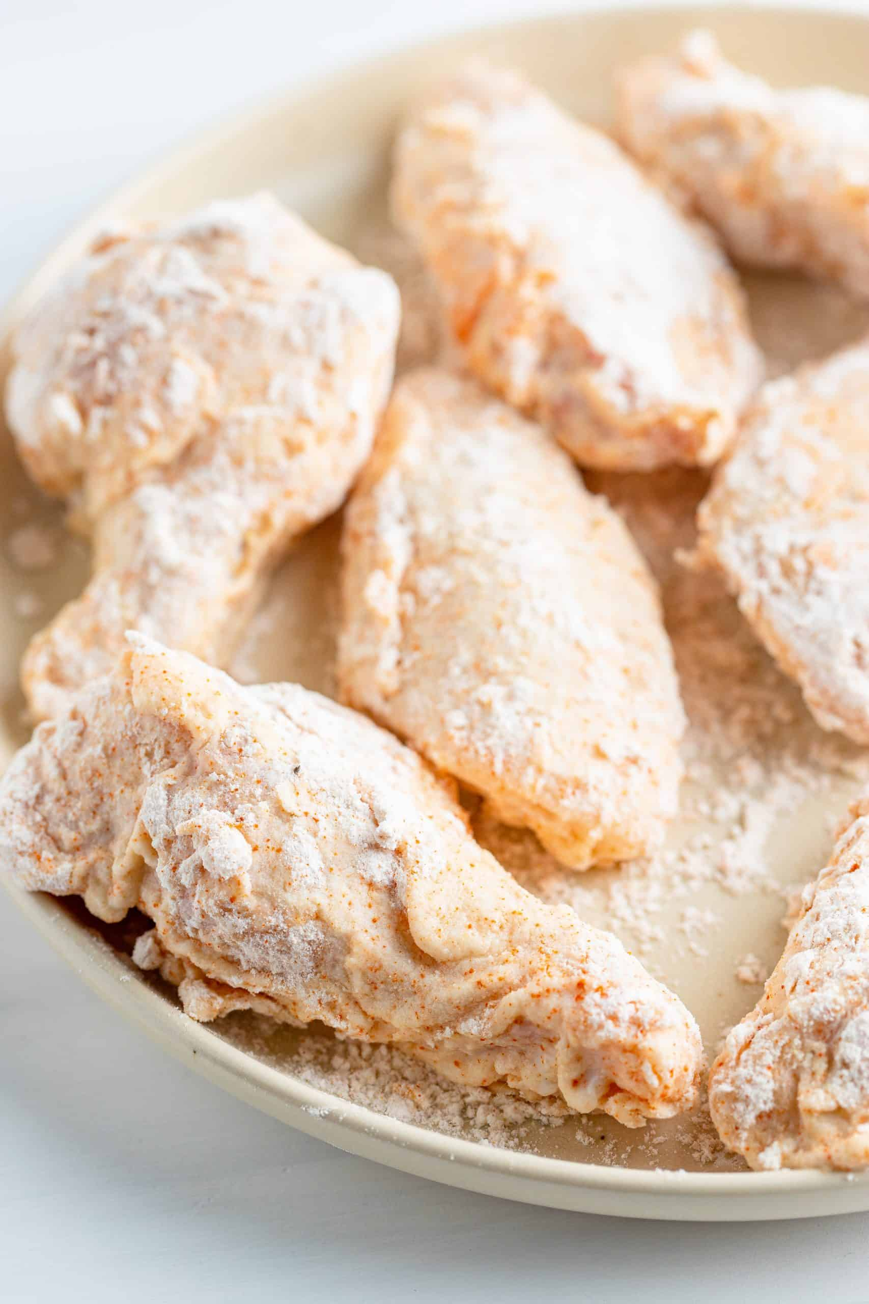 flour coated chicken wings on a large round plate.