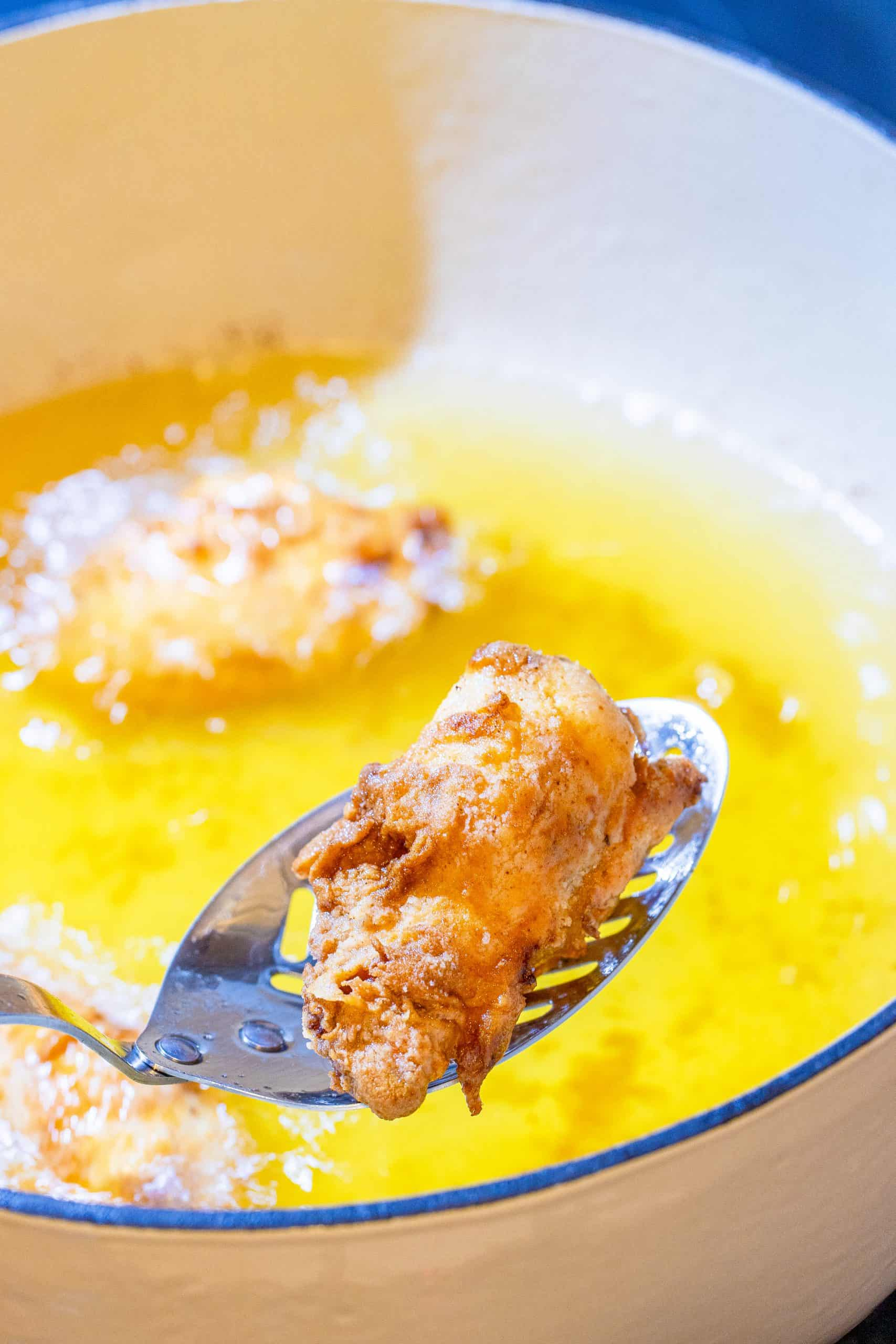 fried chicken wing in a spatula held over a dutch oven with oil.