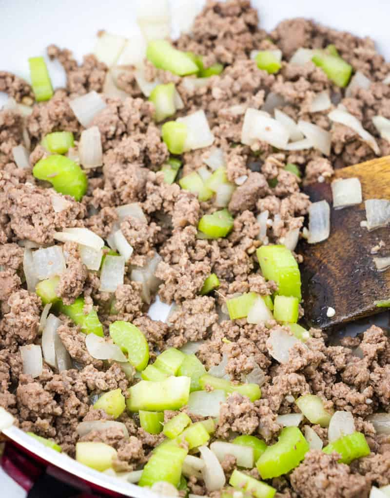 ground beef, celery, onion in a skillet with a wooden spoon.