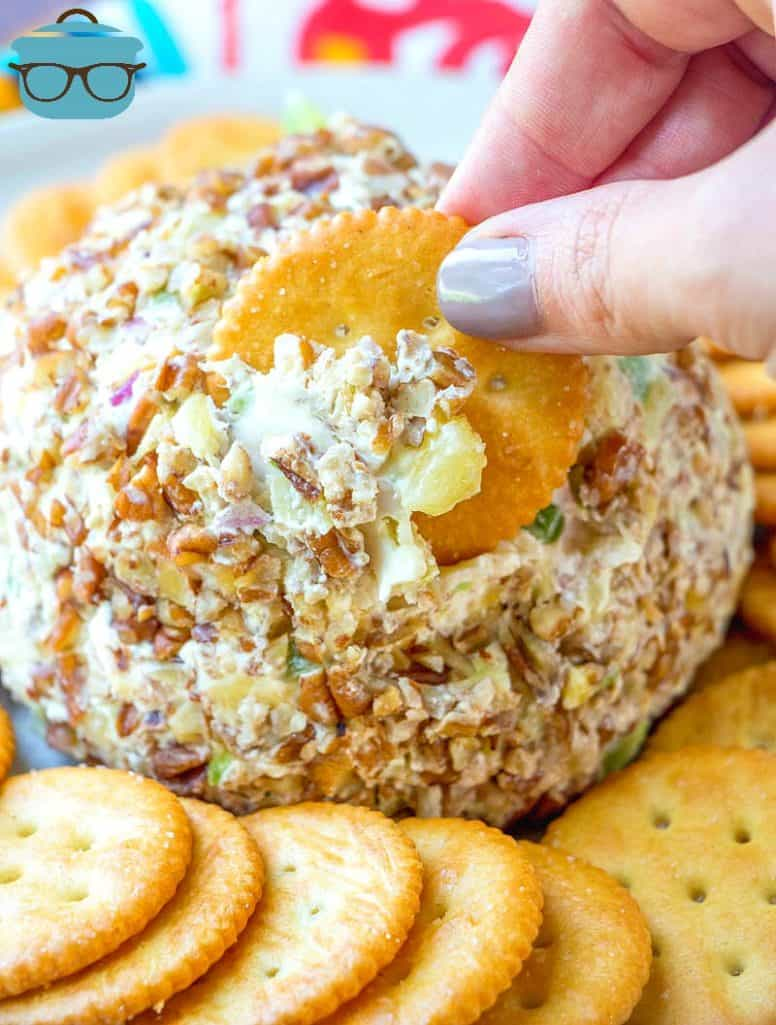 hand shown dipping a Ritz cracker into cheeseball surrounded by additional butter crackers