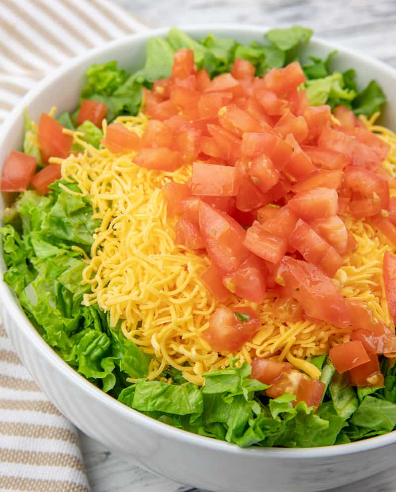 shredded lettuce, cheddar cheese, diced tomatoes, crushed Doritos and taco seasoned ground beef in a large bowl