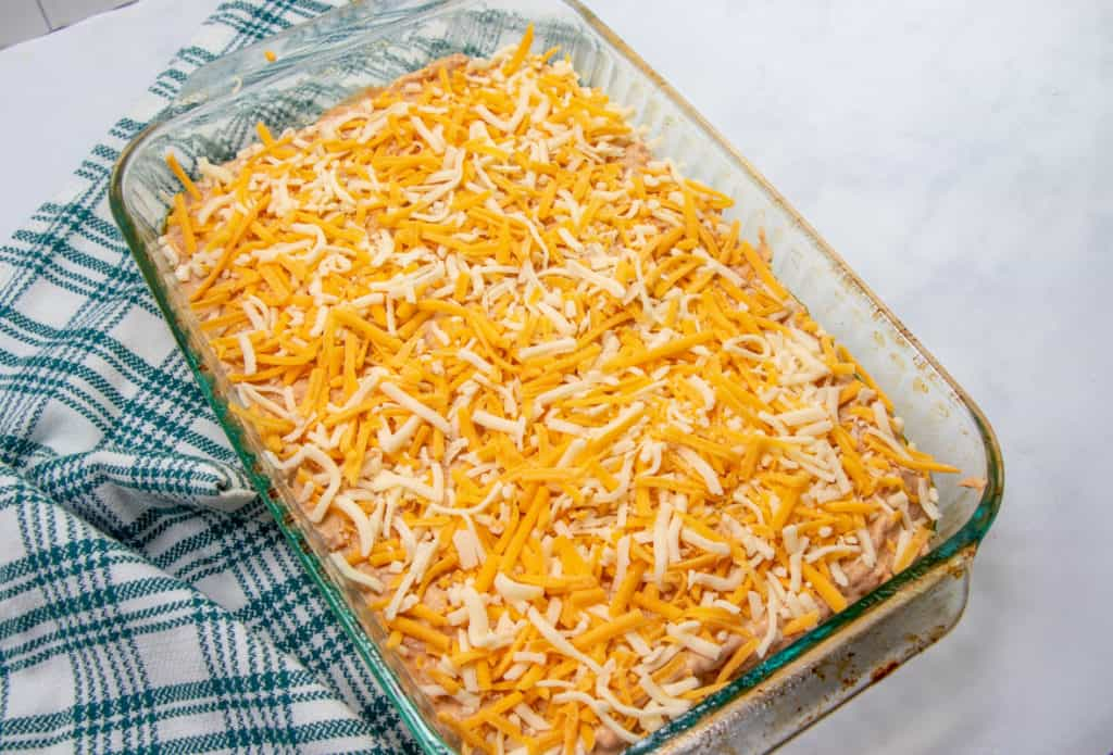 warm bean dip mixture spread into a 9X13 baking dish topped with shredded cheeses
