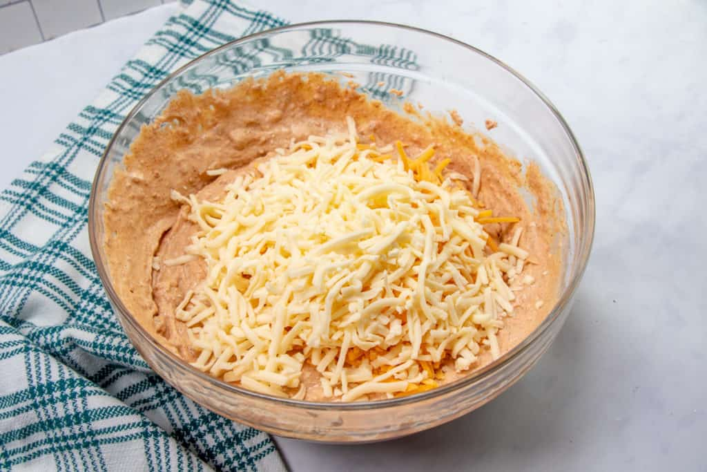 salsa, taco seasoning and cheese added to refried bean mixture in a bowl