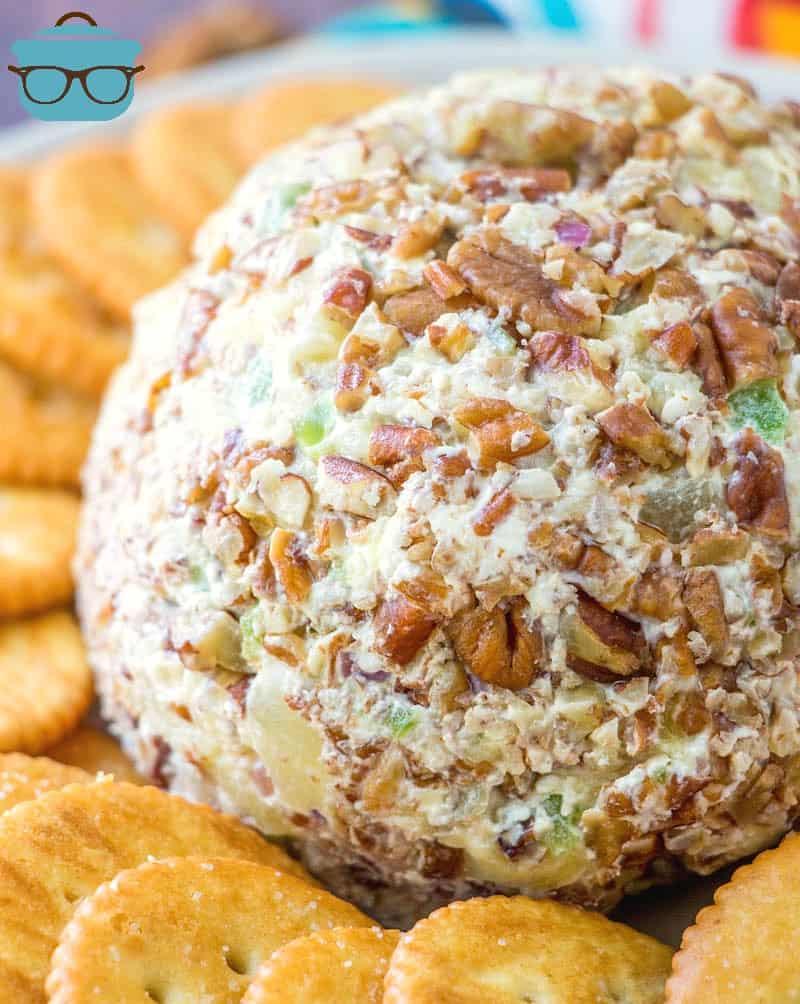 close-up do melhor cheeseball de abacaxi revestido em nozes esmagadas e servido em uma bandeja com biscoitos