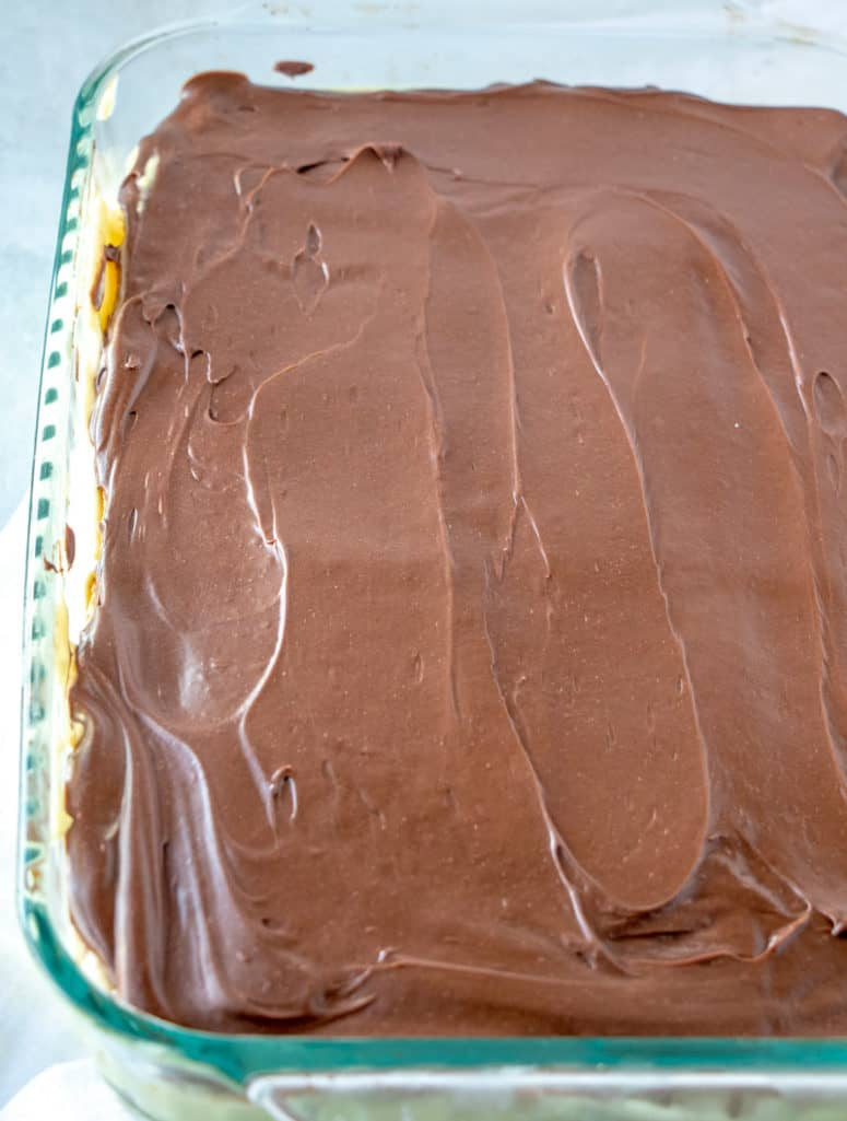 chocolate frosting spread on top of eclair cake
