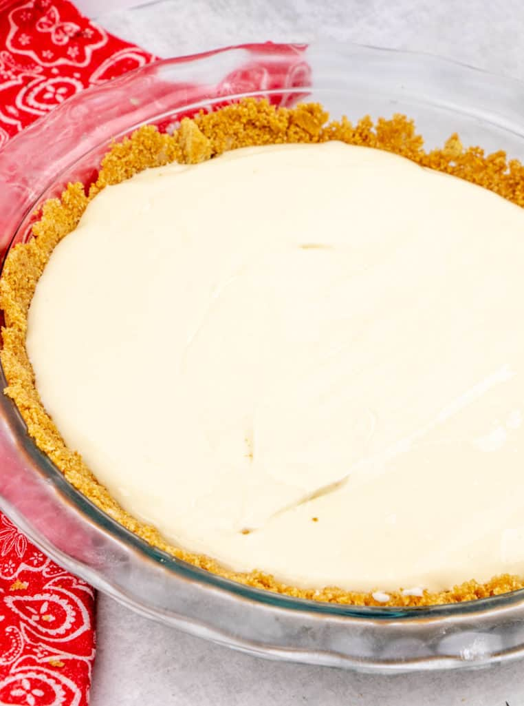 homemade cheesecake filling poured into prepared graham cracker crust