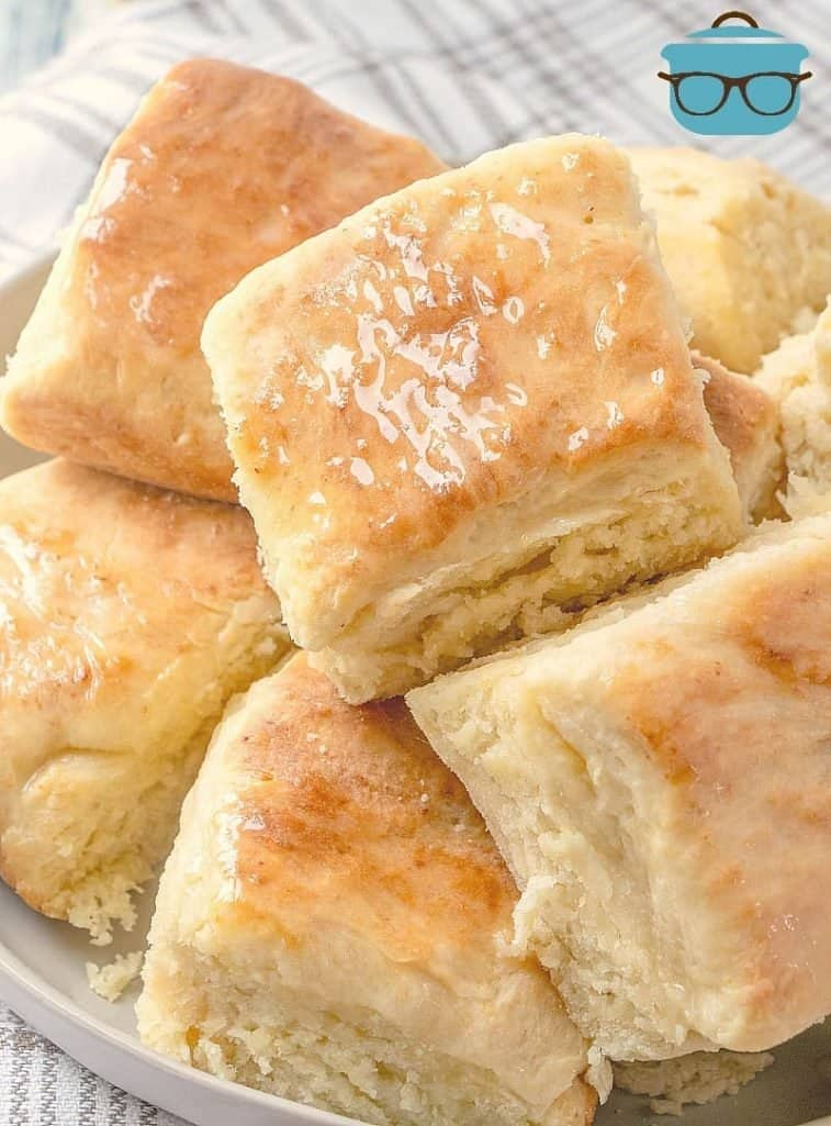 Easy Yeast Biscuit rolls piled on a plate with melted butter on top
