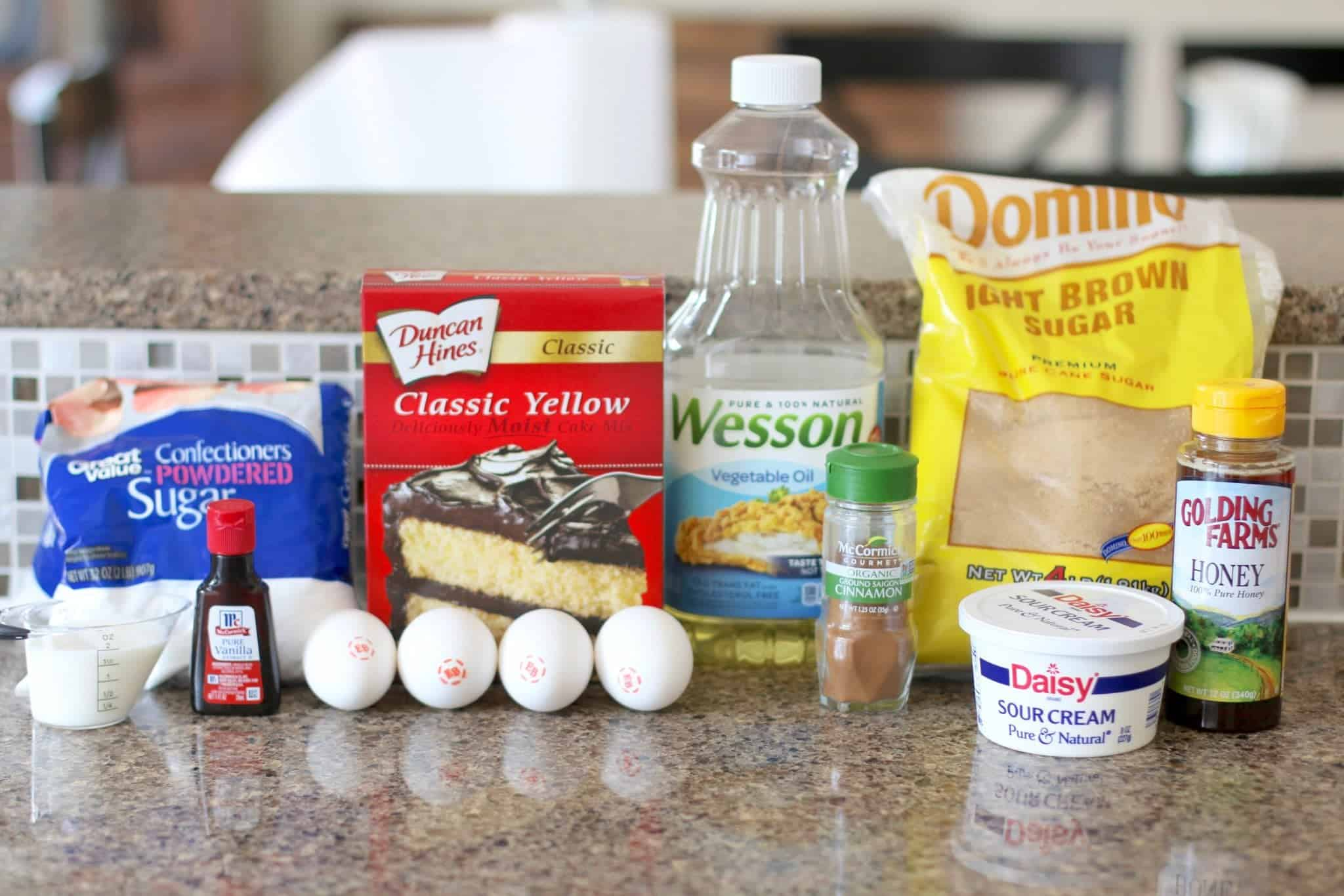 yellow cake mix, brown sugar, eggs, sour cream, oil, honey, cinnamon, vanilla extract, powdered sugar.