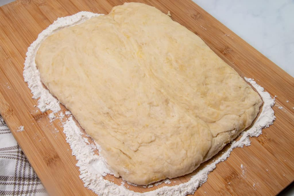 rolled out yeast roll dough on a floured cutting board