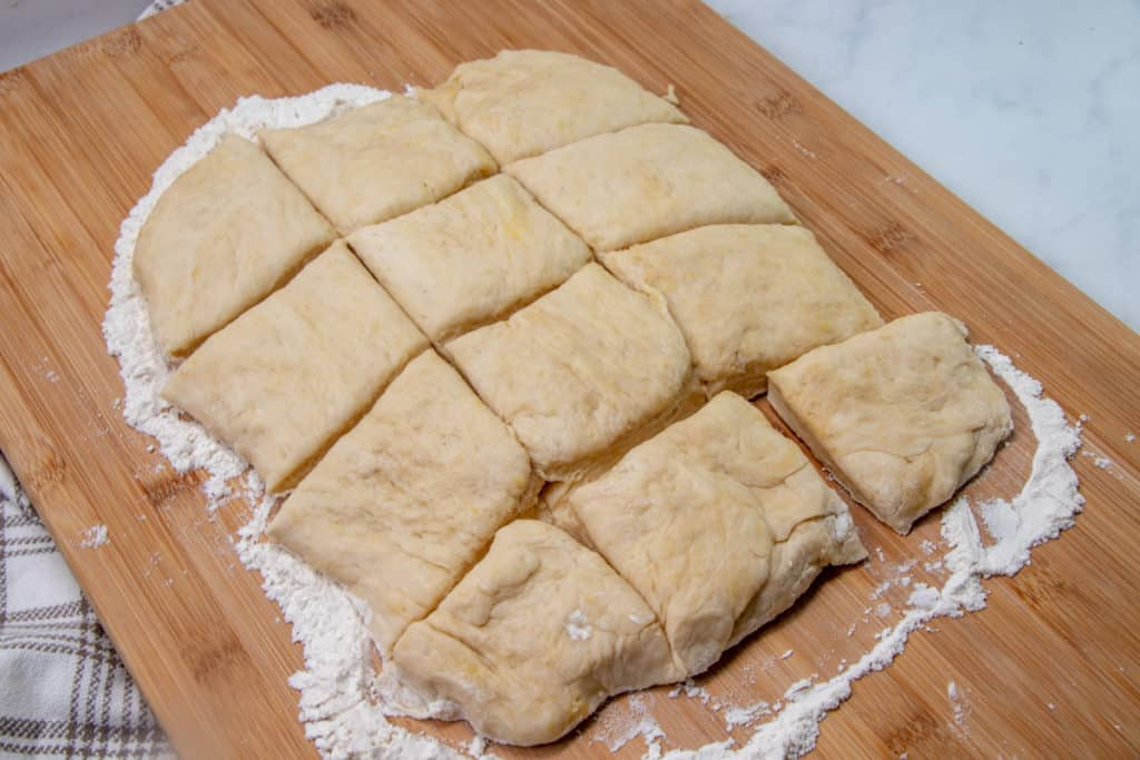 yeast roll biscuit roll dough cut into 12 squares on a floured surface