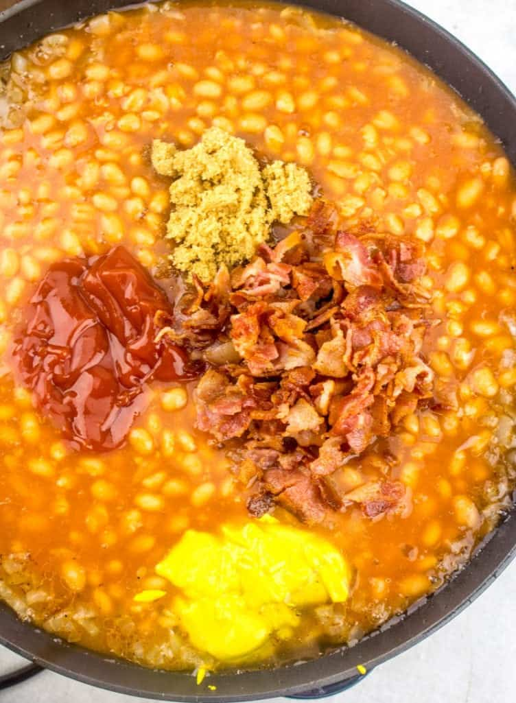 pork and beans, cooked bacon, brown sugar, maple syrup, ketchup, mustard all mixed together in a very large skillet