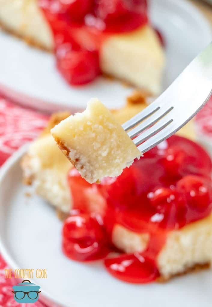 Easy cheesecake with homemade graham cracker crust, slice on a white plate with fork