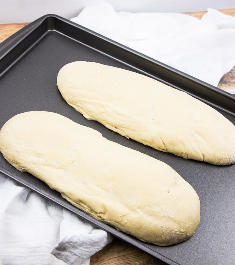 two French bread loaves rising on a large baking sheet