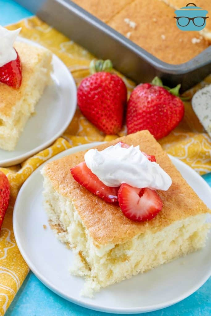Hot Milk Sponge Cake served on a plate with fresh strawberries and whipped cream