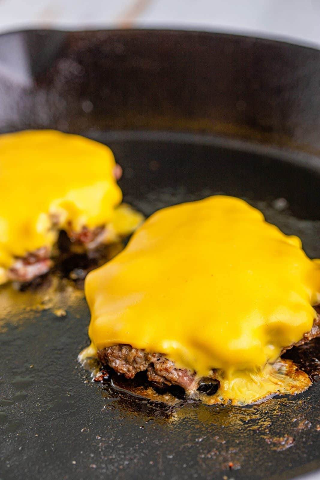 melted cheese shown on top of cooked steak burgers in a black cast iron skillet