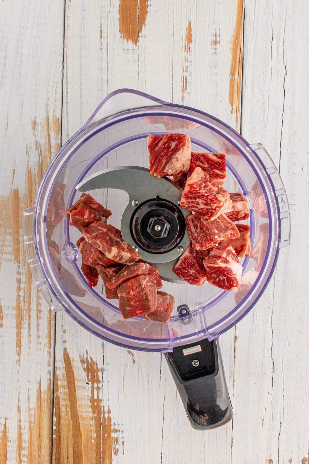 cubed meat shown in the bowl of a food processor