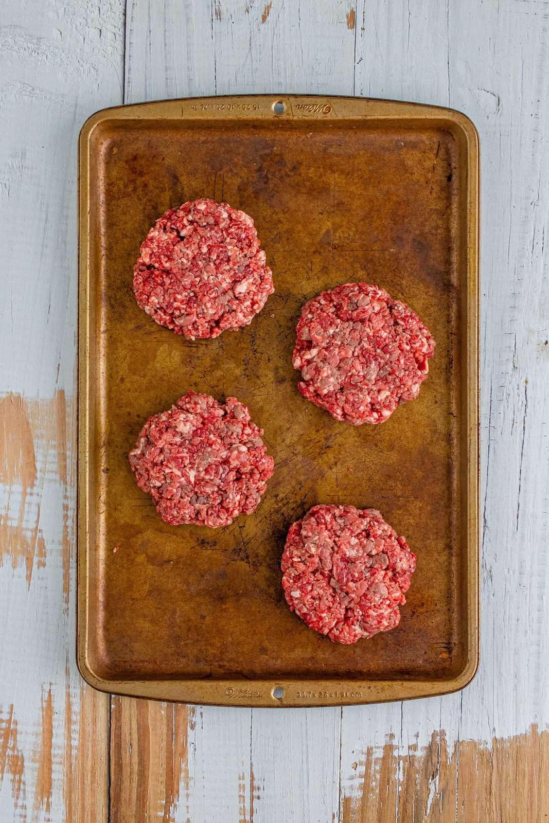 raw shaped steakburger patties on a baking sheet