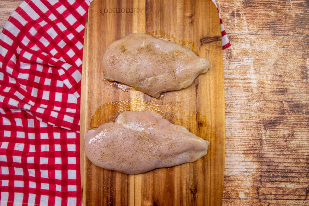 seasoned chicken breasts on a wooden cutting board