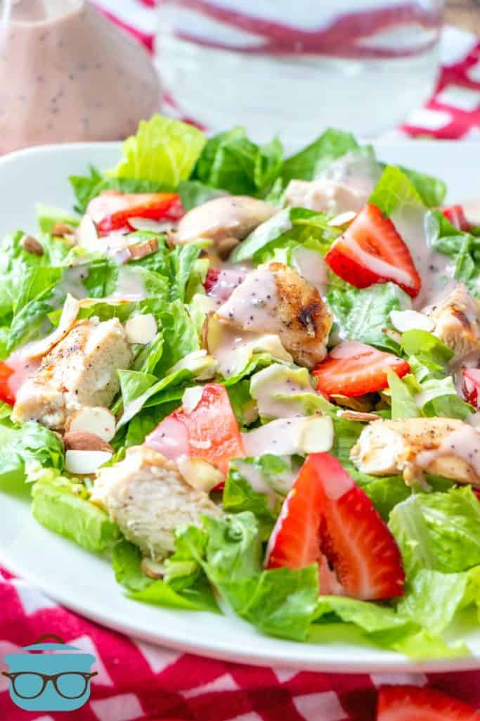 Strawberry Grilled Chicken Salad pictured on a large white plate with a red and white kitchen towel on the side