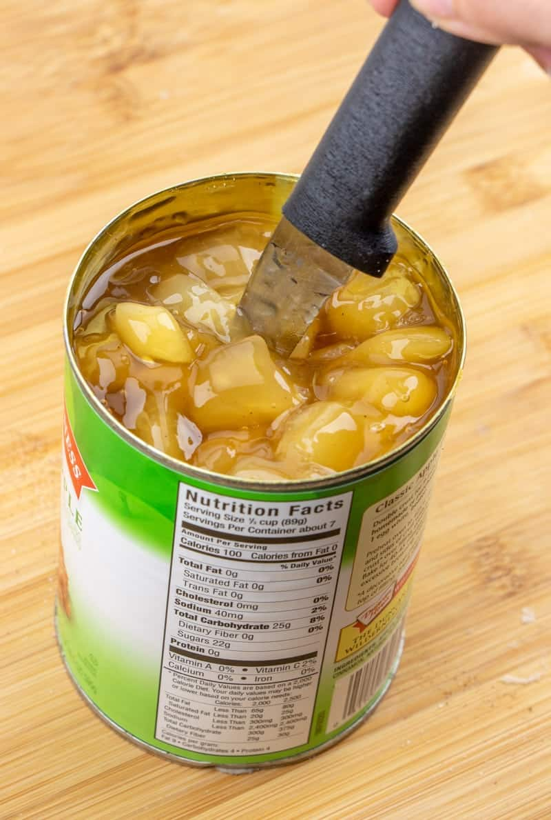 chopped apple pie filling in the can with a knife.