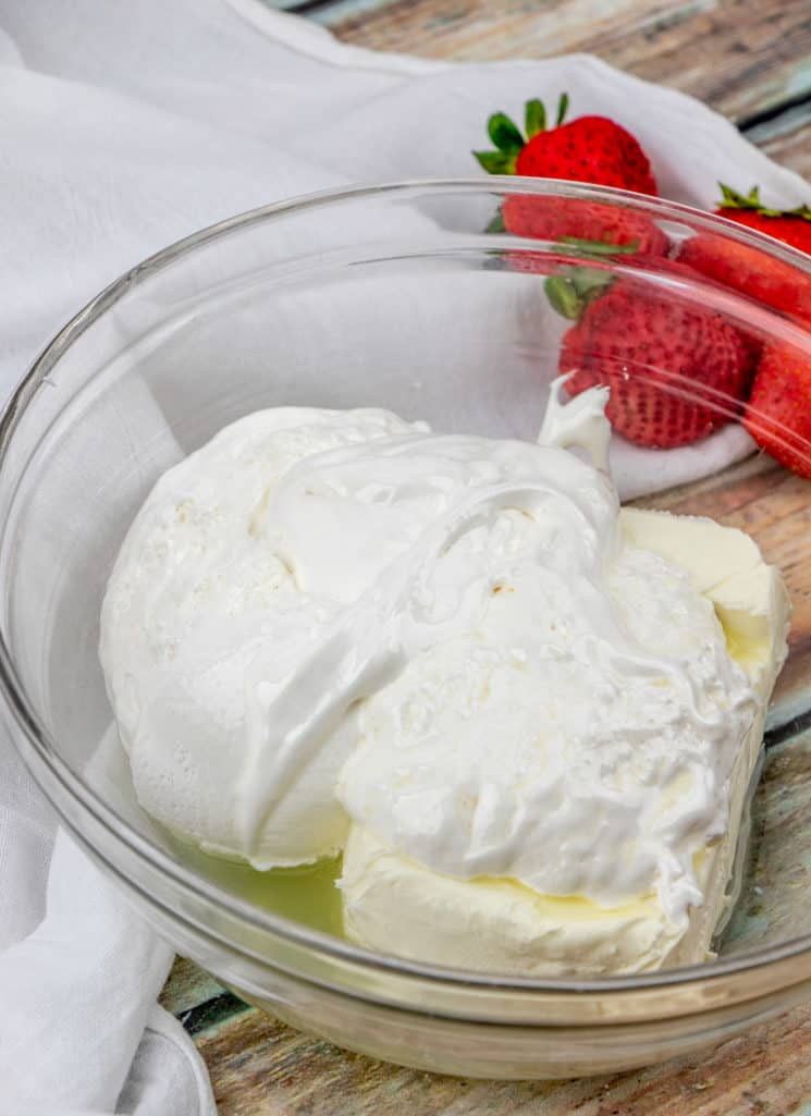 pictured, cream cheese, marshmallow fluff, lemon juice in a clear bowl with strawberries on the side