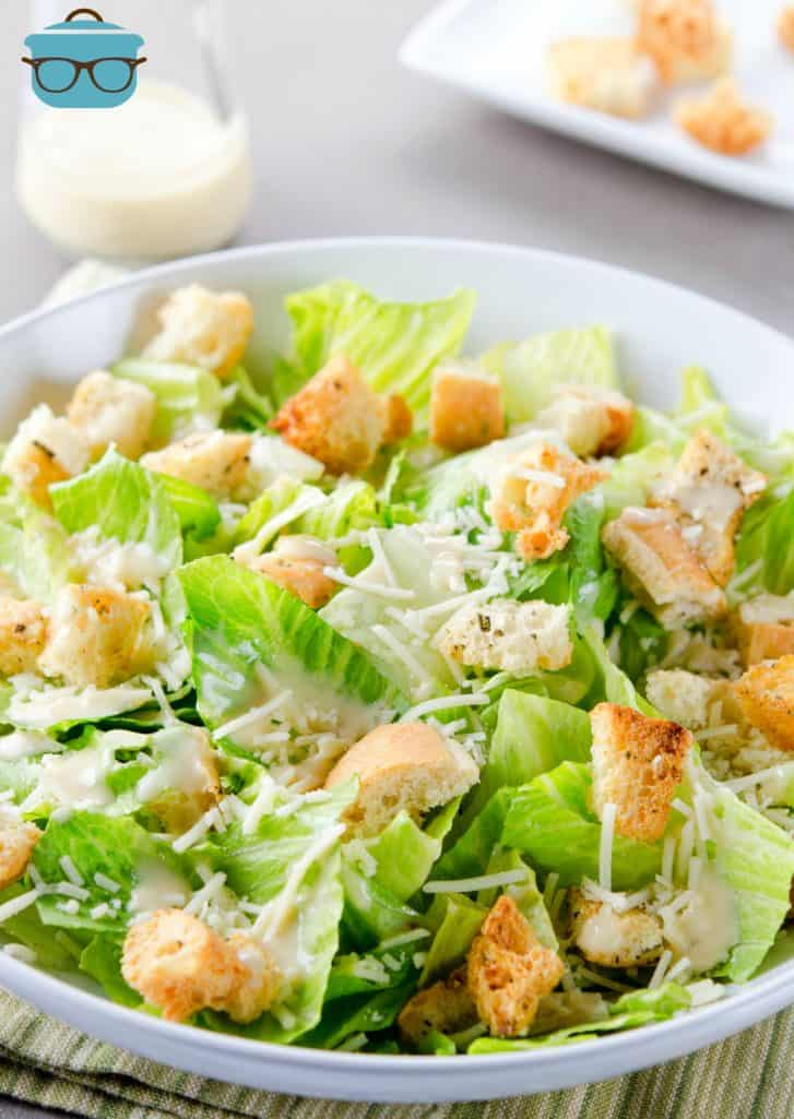 Caesar salad in a white bowl with homemade dressing drizzled on top