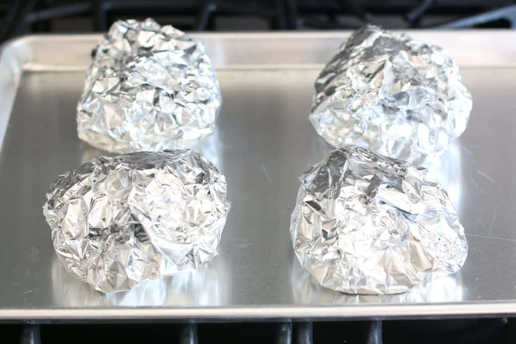 folded up potato packs on a baking sheet