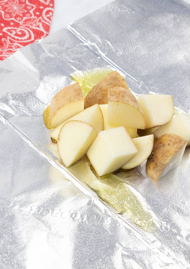 diced russet potatoes and butter on an aluminum foil sheet