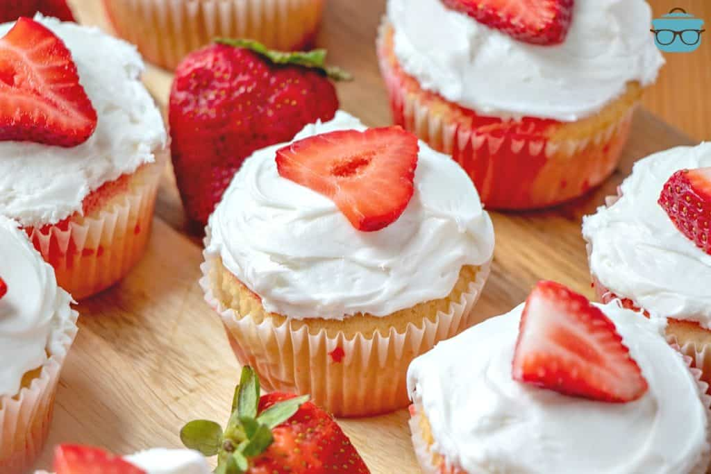 Strawberry Jell-o Poke Cupcakes topped with a fresh sliced strawberry