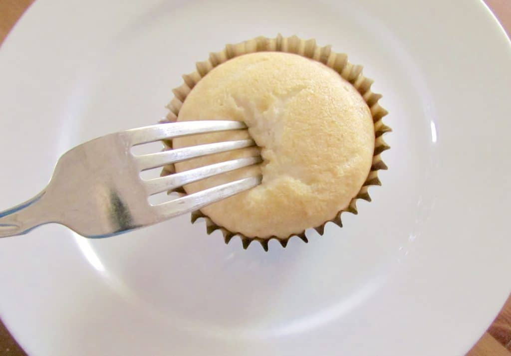 poking holes in a cupcake with a fork