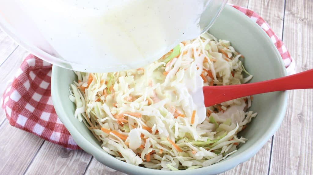pouring coleslaw dressing over shredded cabbage