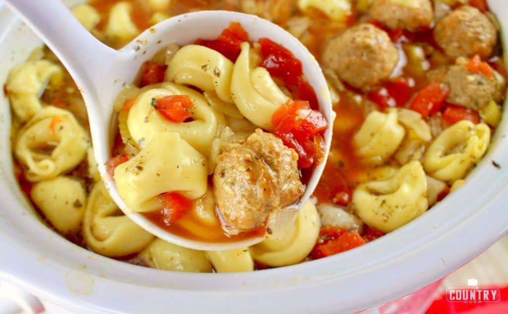 ladle of meatball tortellini soup