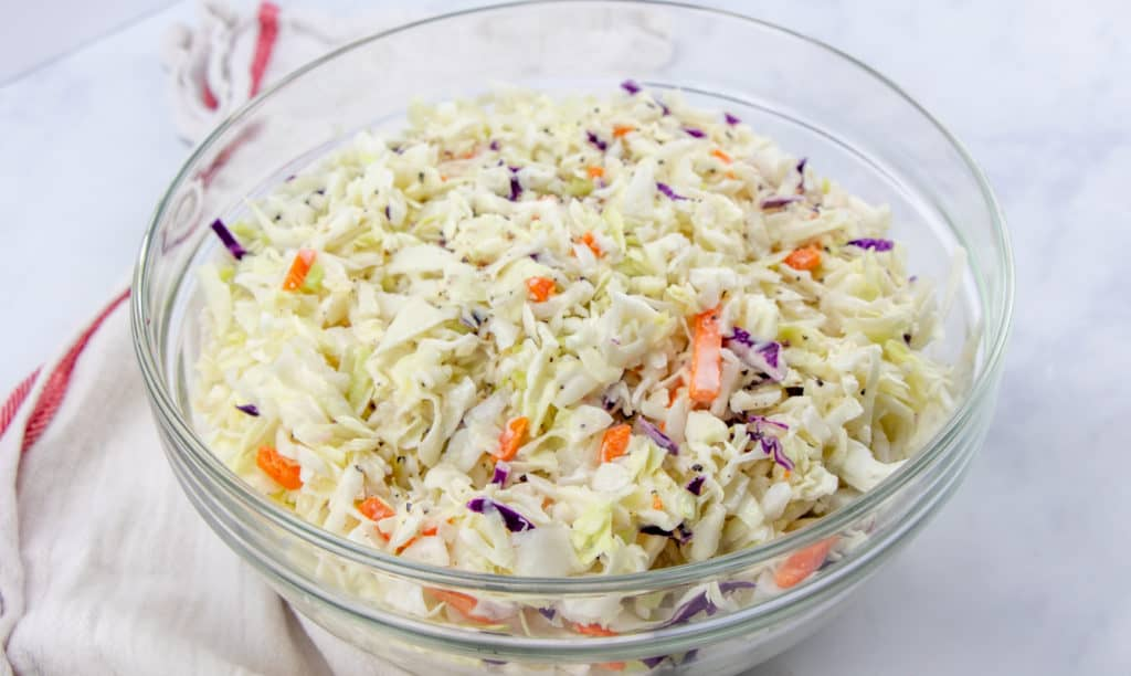 Cole slaw dressing poured over cabbage Cole slaw mixture in a large bowl