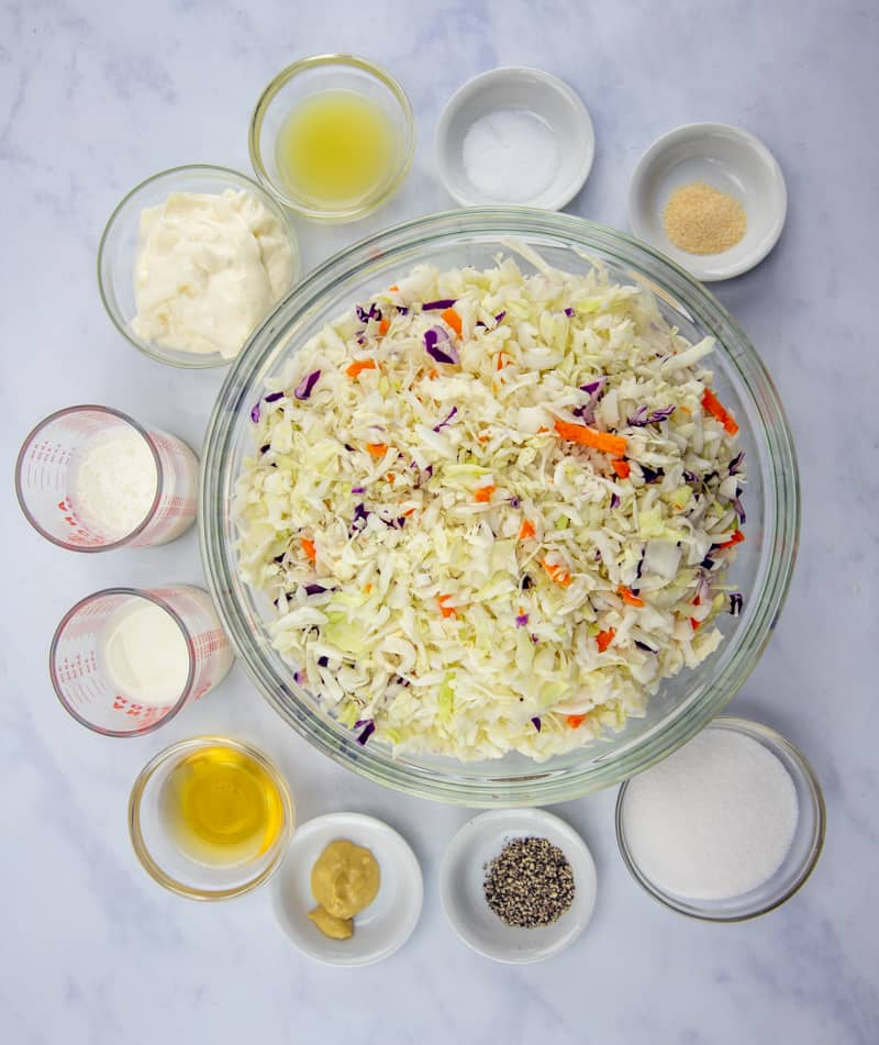 coleslaw ingredients: coleslaw mix, sugar, milk, mayonnaise, buttermilk, Dijon mustard, apple cider vinegar, lemon juice, freshly grated onion (or onion powder), salt, freshly ground black pepper
