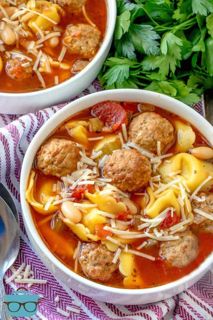 wo white soup bowls filled with meatball tortellini soup with cilantro pictured to the side