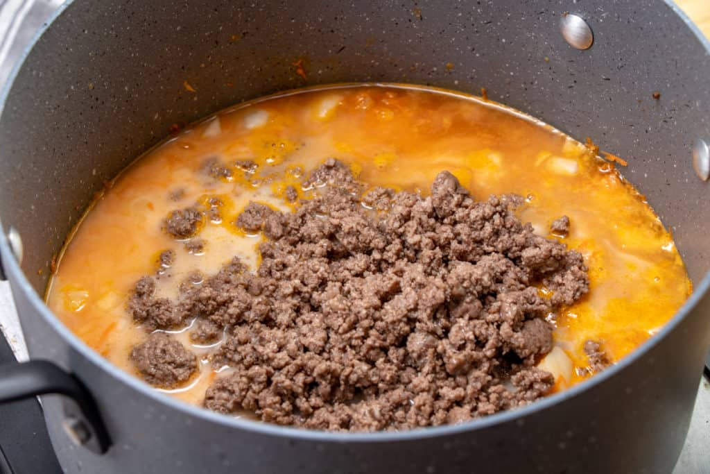 cooked ground beef added to soup mixture in a large pot
