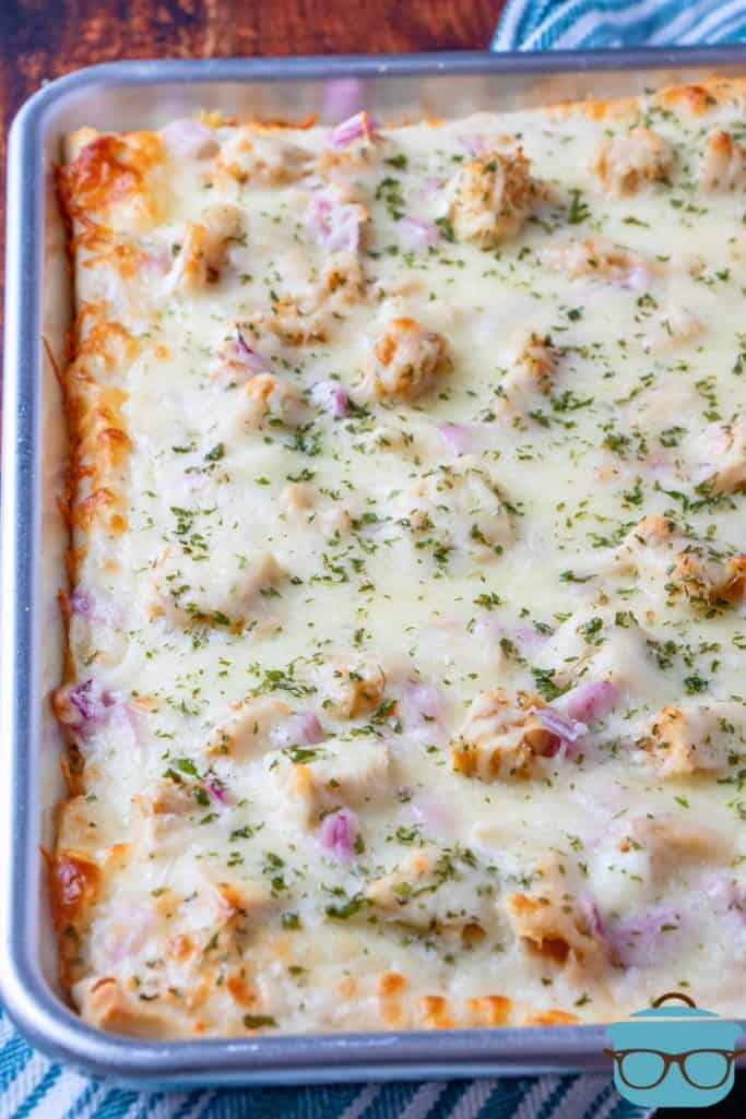 fully baked chicken Alfredo pizza on a stainless steel baking sheet