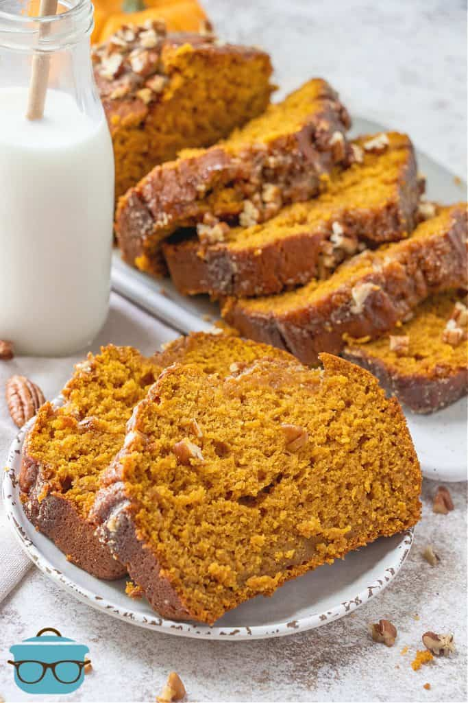 sliced pumpkin bread shown on a white plate with a bottle of milk in the background
