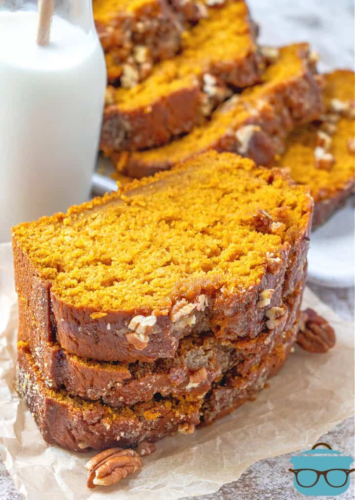Homemade Pumpkin bread, slices shown stacked on parchment paper with a bottle of milk in the background