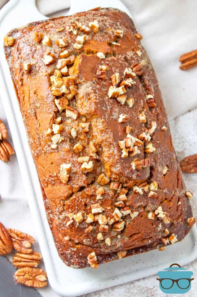 fully baked pumpkin bread with glaze and chopped pecans shown on a white platter