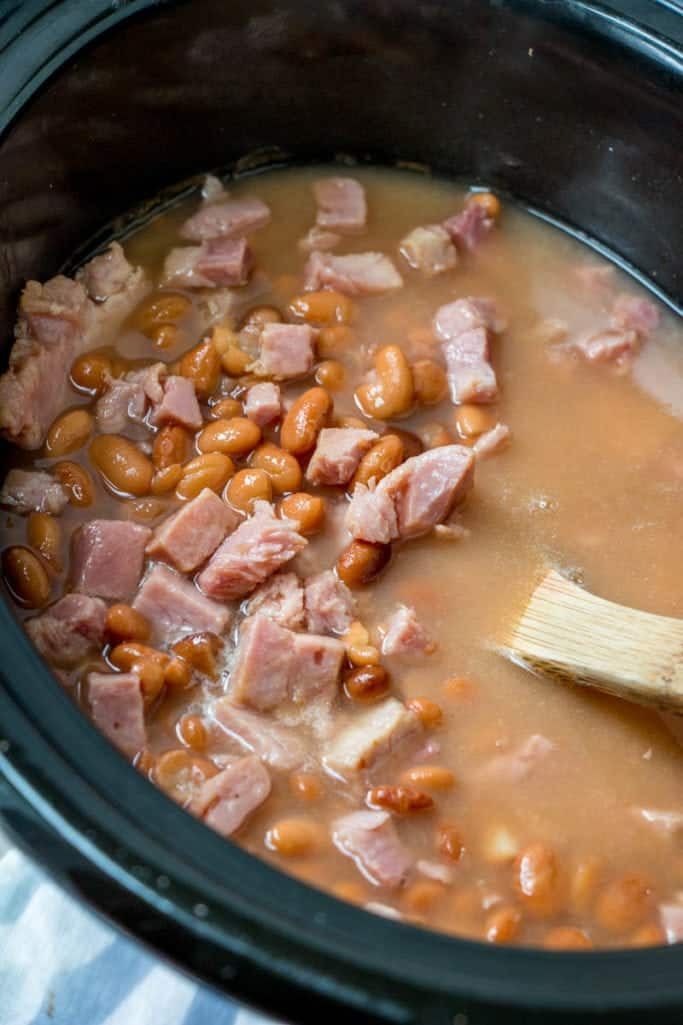 slow cooker soup beans and ham in an oval crock pot
