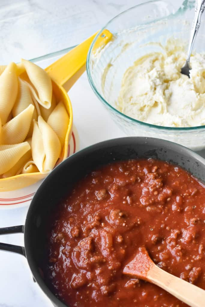 ground beef tomato sauce in a pan, cooked shells, ricotta