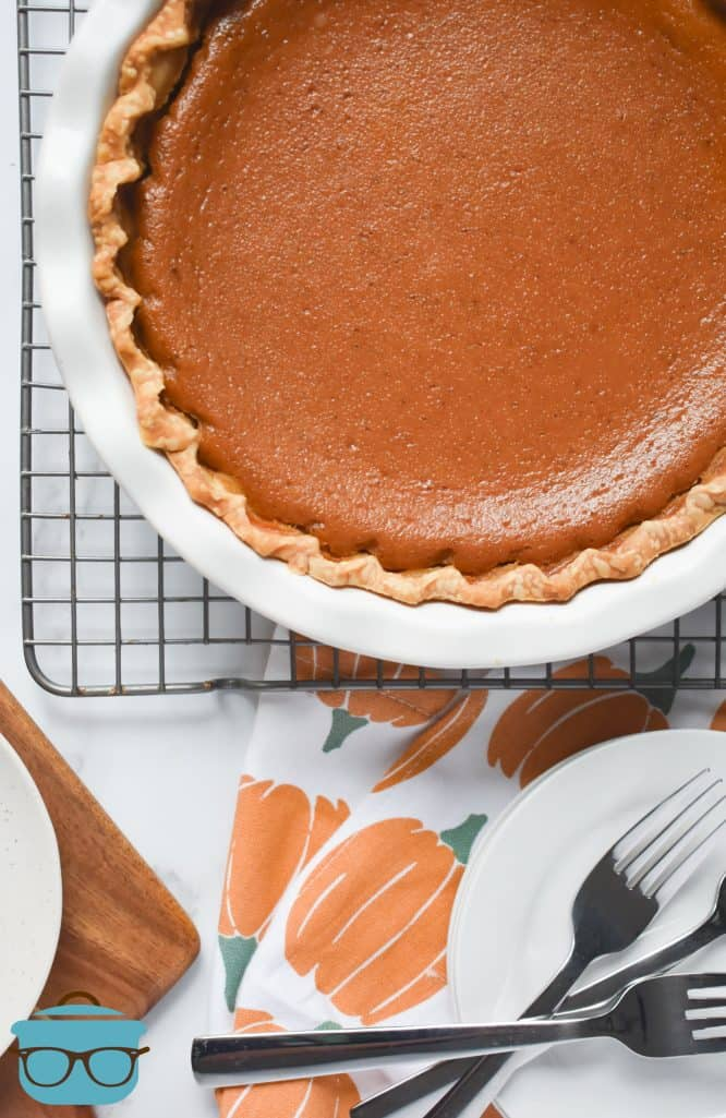 fully baked Pumpkin Pie on a cooling rack with plates on the side