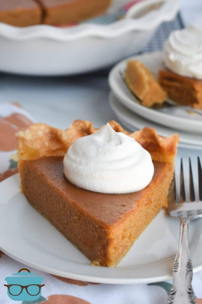 slice of Brown Sugar Pumpkin Pie on a plate topped with whipped cream with a fork on the side