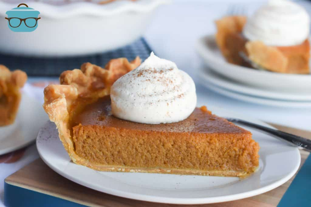 slice of pumpkin pie on a small white plate, topped with a dollop of whipped cream