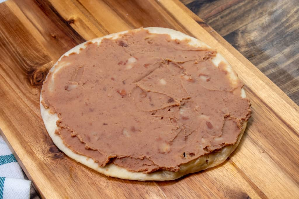 refried beans spread onto fried tortilla