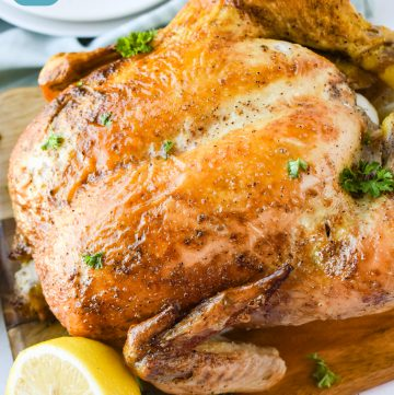 Perfect Roast Chicken on a cutting board with a sliced lemon