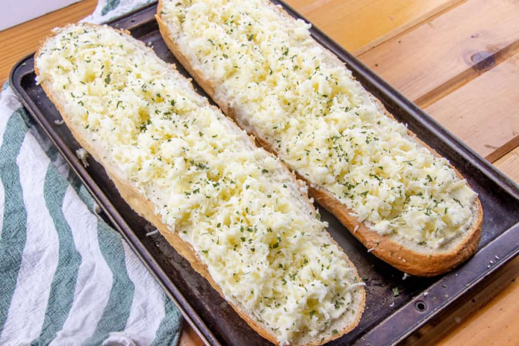 mozarella mayonnaise cheese mixture spread evenly across garlic butter on French bread loaf