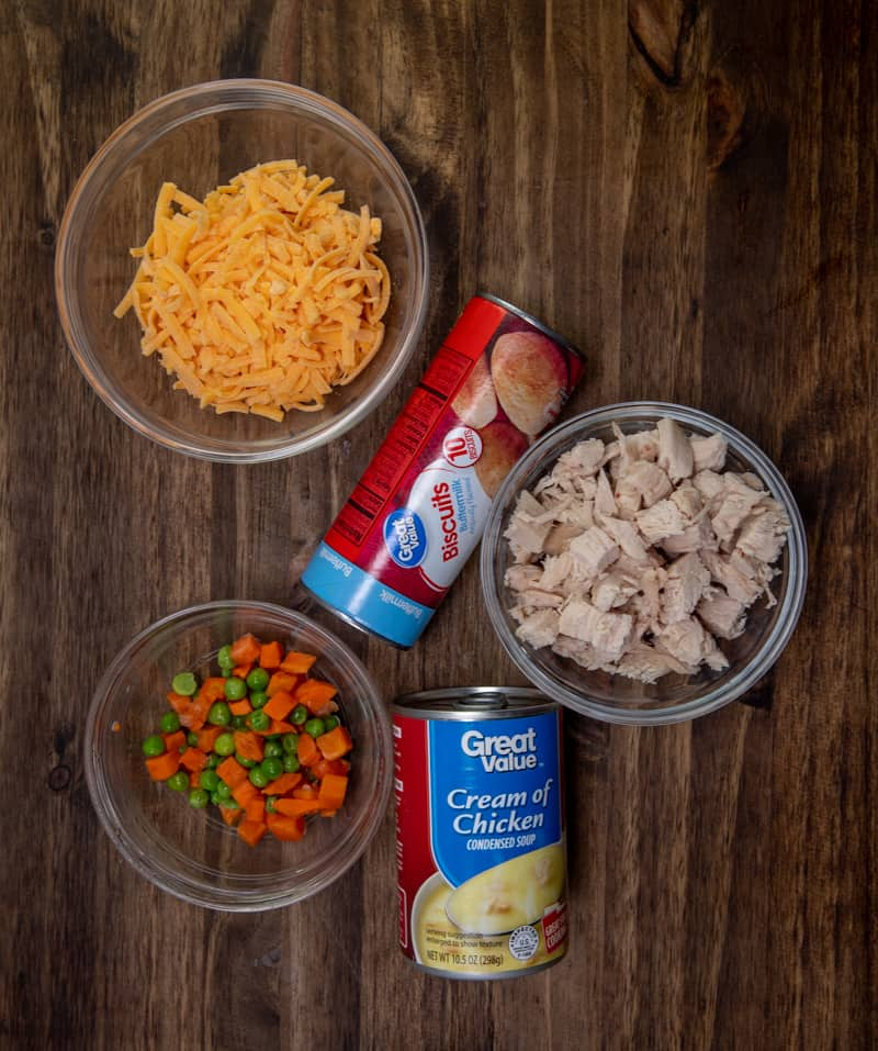 refrigerated biscuits, cooked chicken, cream of chicken soup, shredded cheddar cheese, frozen peas and carrots